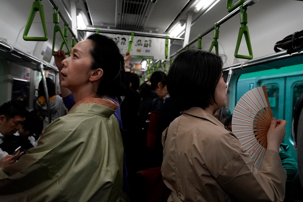 A woman wearing a kimono looks at a train route map while travelling in a Yamanote Line train in Tokyo. (AP Photo/Jae C. Hong)