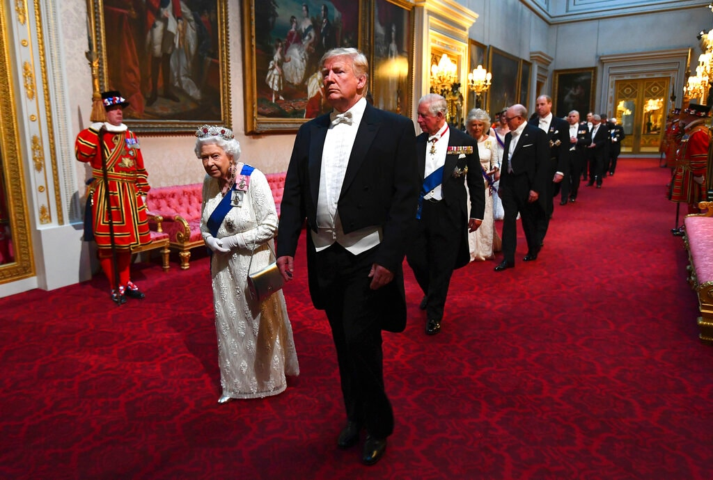 Queen Elizabeth II, center left, U.S. President Donald Trump, center, and others arrive through the East Gallery ahead of the State Banquet at Buckingham Palace in London, Monday, June 3, 2019. Trump is on a three-day state visit to Britain. (Victoria Jones/Pool Photo via AP)