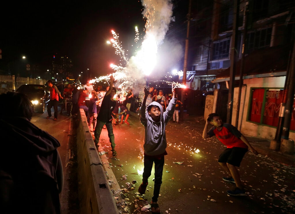 Indonesian youths light firecrackers and flares as they celebrate the end of the fasting month of Ramadan on a street in Jakarta, Indonesia, Tuesday, June 4, 2019. People in the world's most populous Muslim country flocked to the streets in the capital on the eve of Eid al-Fitr which marks the end of the holiest month in Muslim calendar. (AP Photo/Dita Alangkara)