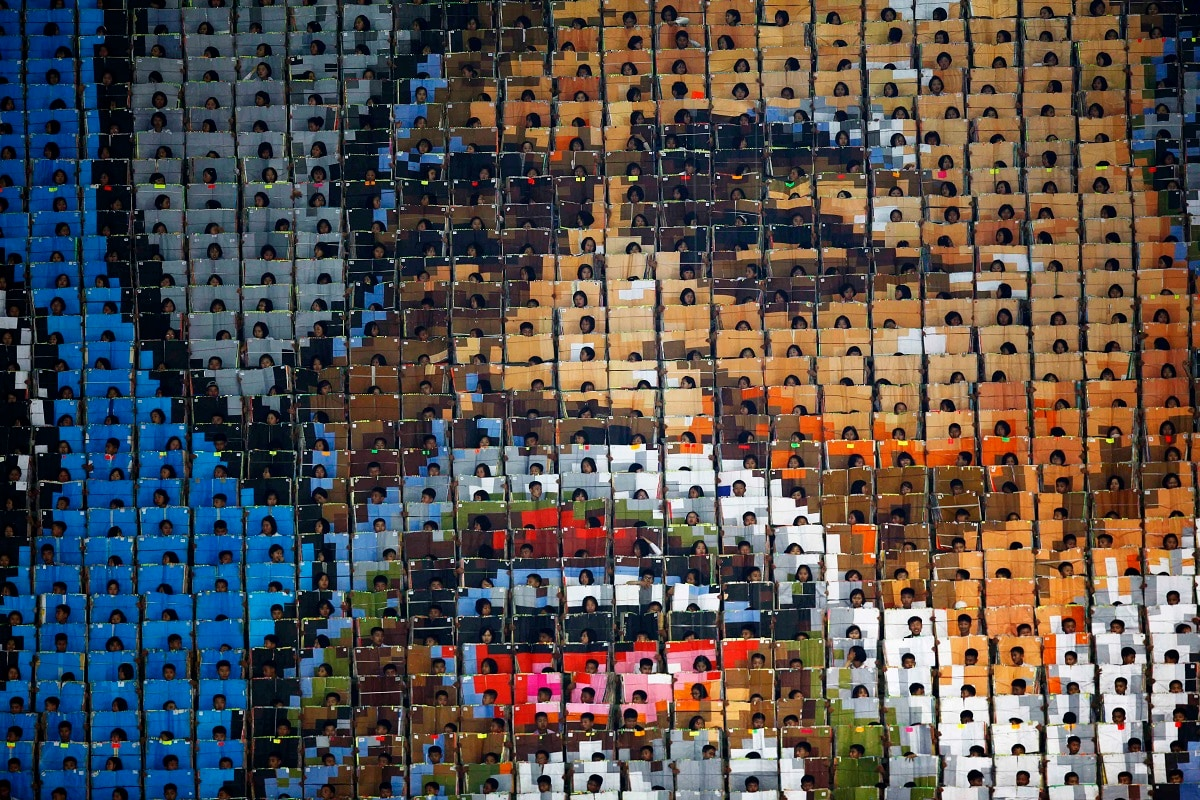 Students hold cards to form a pattern of smiling face of an old man during the mass game performance of