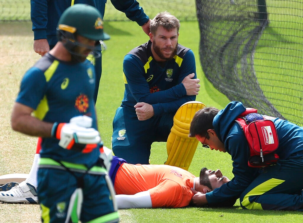 Australia's David Warner, center, reacts as a paramedic attends to a net bowler after he was hit on his head by a shot played by Warner during a training session ahead of their Cricket World Cup match against India. (AP Photo/Aijaz Rahi)