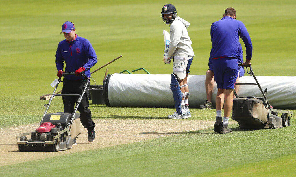 India's Rohit Sharma, center, inspects the pitch as groundsmen work during a training session ahead of their Cricket World Cup match against Australia. (AP Photo/Aijaz Rahi)