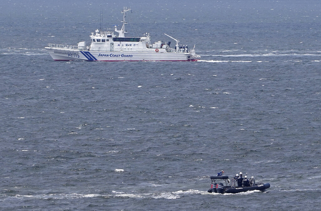 Japanese coast guard ship and security personnel patrol at sea near the venue of G20 Finance Ministers' and Central Bank Governors' meeting. (AP Photo/Eugene Hoshiko)