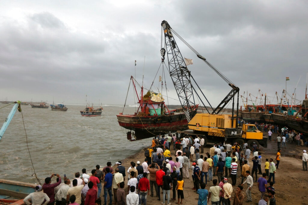 People use a crane to pull a fishing boat ashore on the Arabian Sea coast in Veraval, Gujarat, India, Wednesday, June 12, 2019. (AP Photo/Ajit Solanki)