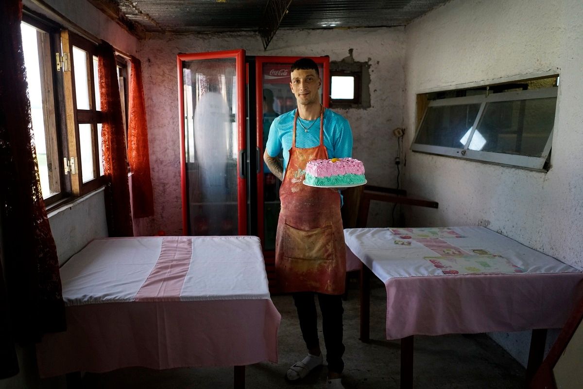 Inmate Nelson Avantti, who runs a bakery inside the Punta de Rieles prison, holds a cake at his bakery at the prison in Montevideo, Uruguay. Money to start businesses like Avantti's comes from inmates' families or from a quasi-bank largely administered by inmates themselves. (AP Photo/Matilde Campodonico)