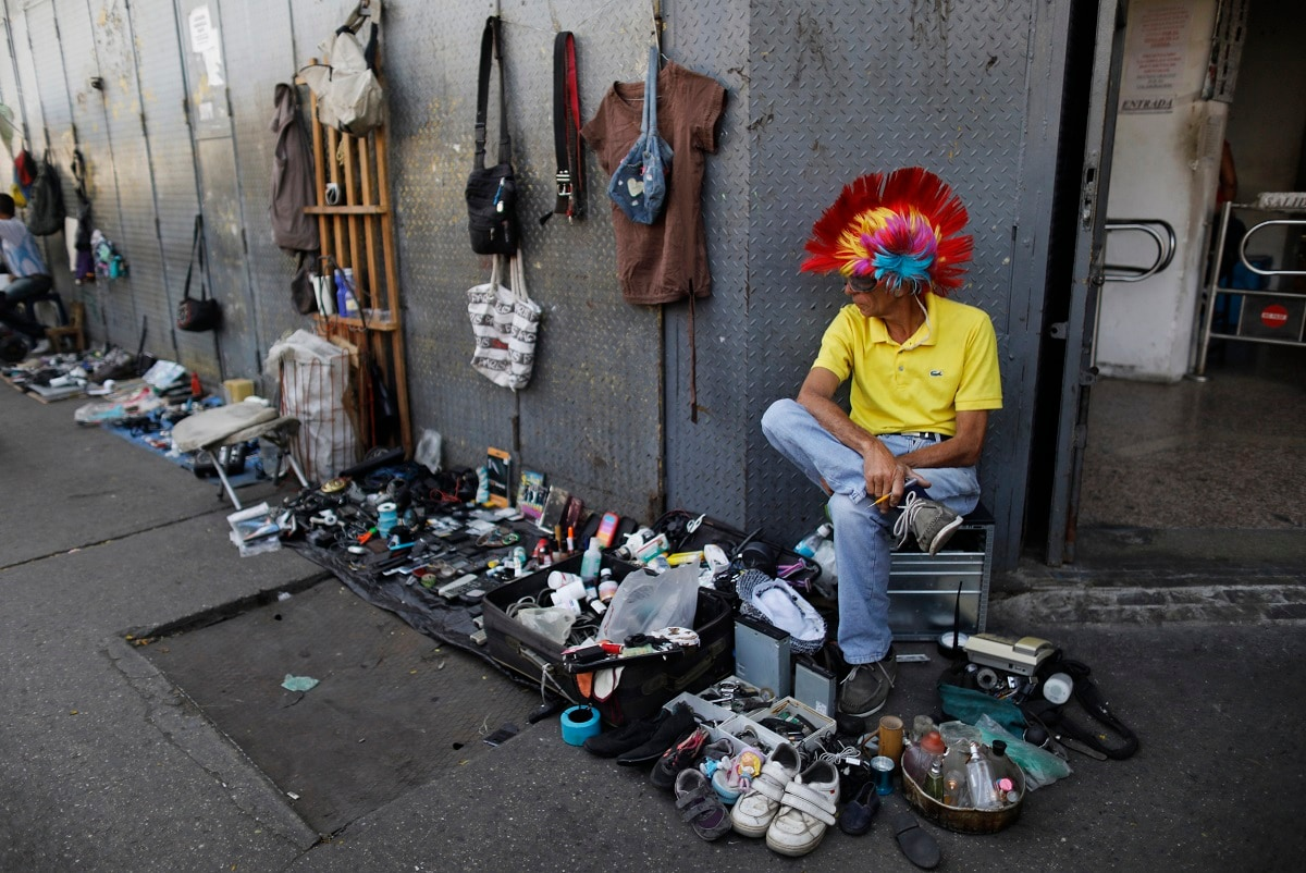 A street vendor sits next to his used items for sale on the sidewalk in Caracas, Venezuela. Attempts by Venezuelans to survive by recycling items that would otherwise be thrown out is, in one sense, positive, according to Elizabeth Cordido, a social psychologist at Metropolitan University in Caracas. But she said