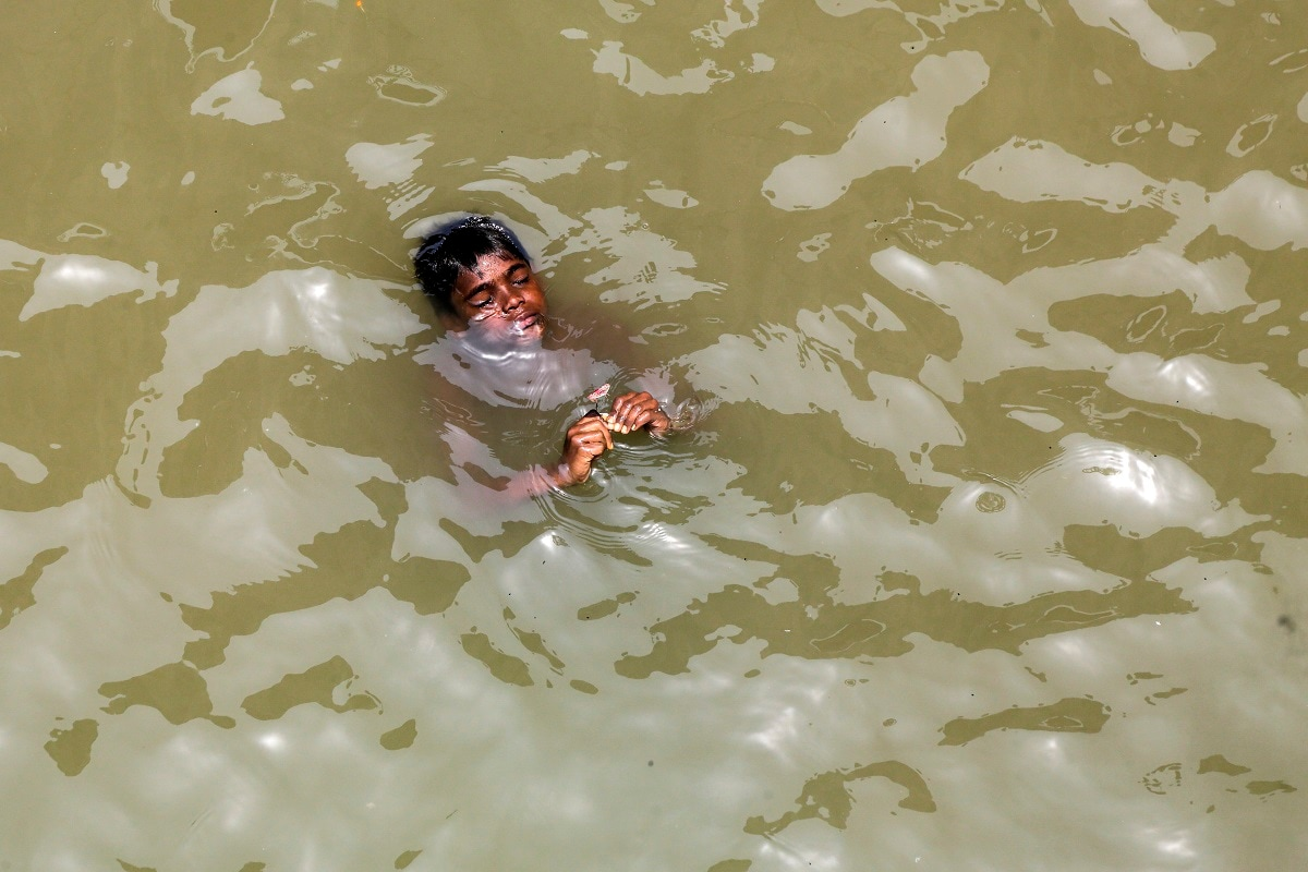 A boy floats in the river Hooghly to beat the heat in Kolkata. (AP Photo/Bikas Das)