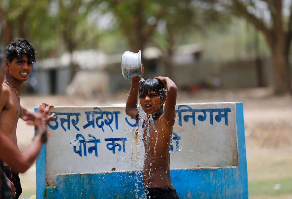 Boys bath at a drinking water tap on a hot day in Prayagraj, India, Sunday, June 16, 2019. Many parts of India are experiencing extreme heat conditions. (AP Photo/Rajesh Kumar Singh)