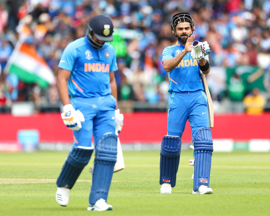 India captain Virat Kohli, right, applauds Rohit as he trudges off the field after losing his wicket. (AP Photo/Aijaz Rahi)