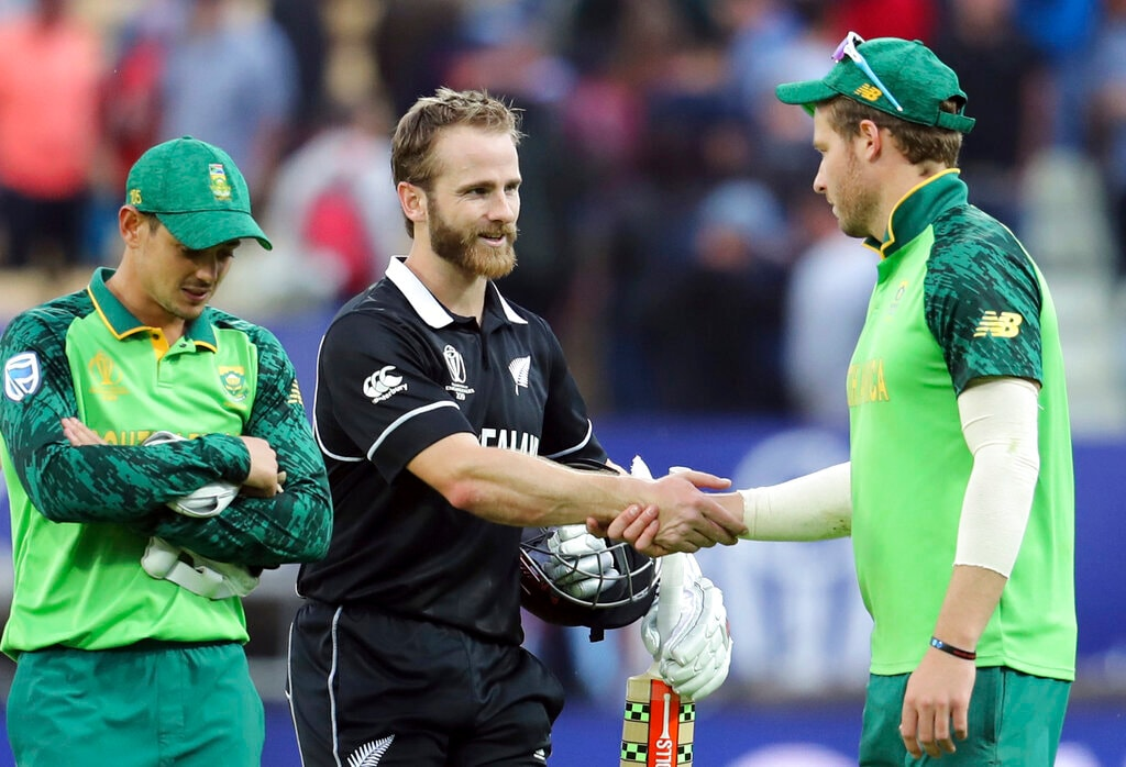 New Zealand's captain Kane Williamson, second from right, shakes and with South Africa's David Miller, right, as teammate Quinton de Kock looks down at end of the Cricket World Cup match between New Zealand and South Africa at the Edgbaston Stadium in Birmingham, Wednesday, June 19, 2019. New Zealand beat South Africa by 4 wickets with 3 balls remaining. (AP Photo/Rui Vieira)