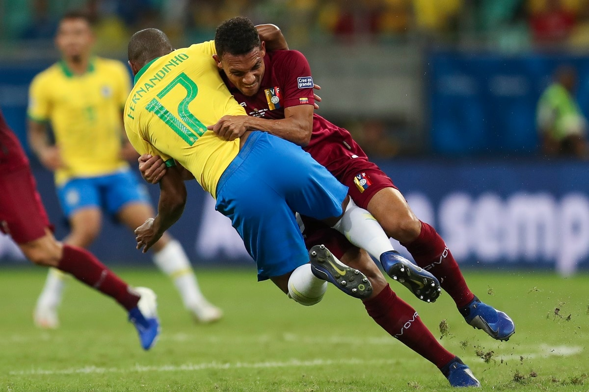 Venezuela's Arquimides Figuera, right, tackles Brazil's Fernandinho during a Copa America Group A soccer match at the Arena Fonte Nova in Salvador, Brazil. (AP Photo/Natacha Pisarenko)