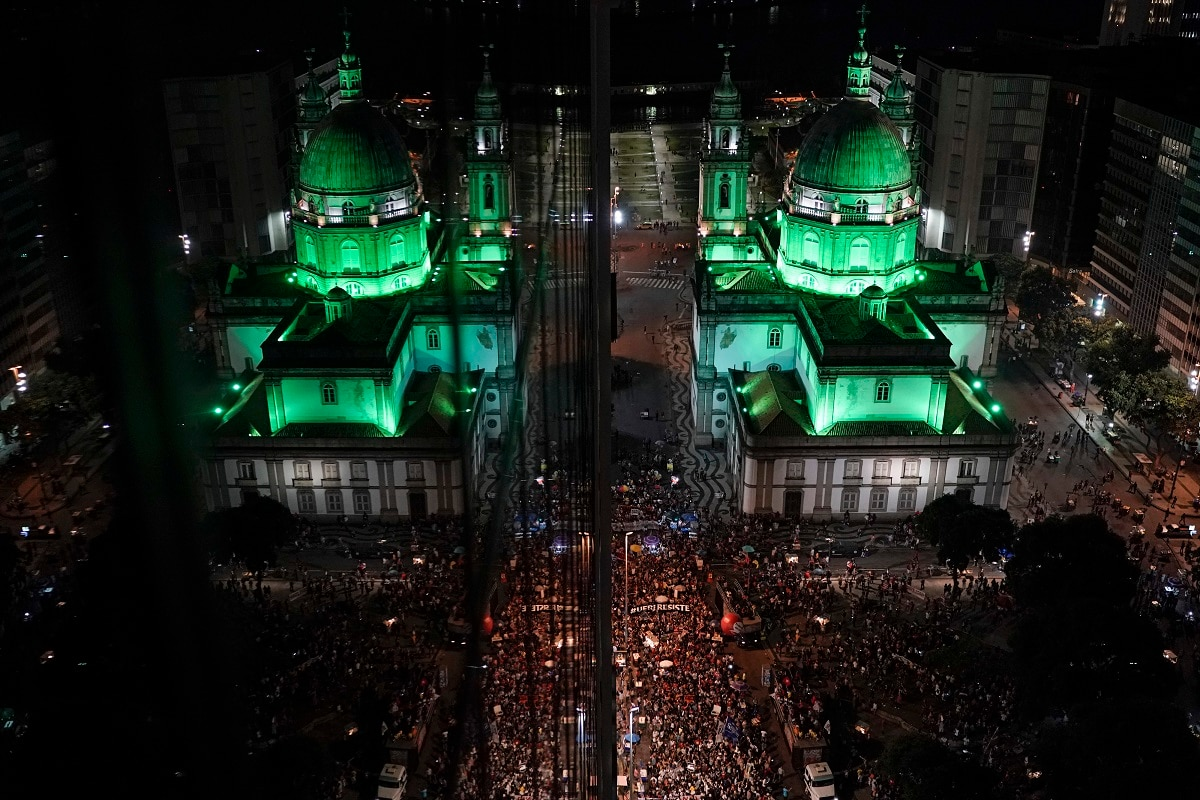 Candelaria church is reflected in a building's windows, left, where people protest government-proposed pension reforms during a strike in Rio de Janeiro, Brazil. The nationwide strike is the first since the arrival of far-right President Jair Bolsonaro on January 1. (AP Photo/Leo Correa)