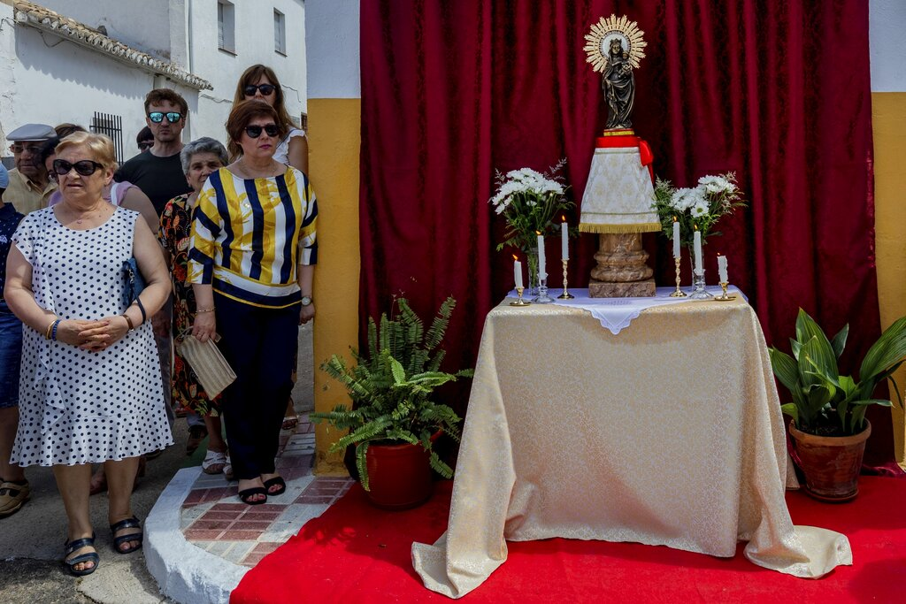 Catholic worshippers stand next to an altar during the sins and dancers Corpus Christi procession in Camunas, central Spain. (AP Photo/Bernat Armangue)