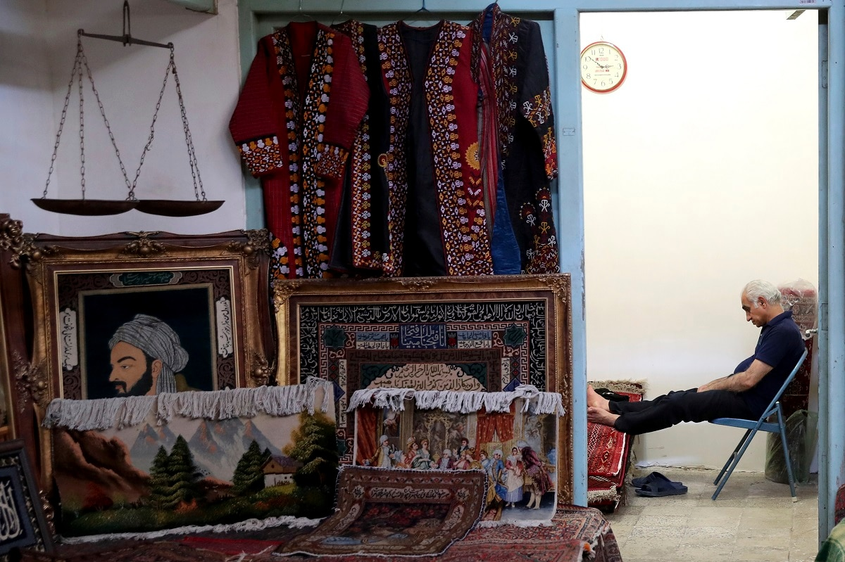 A carpet seller sits at his shop in the old main bazaar in Tehran. In recent weeks, Iran has threatened to break out of the deal unless European powers mitigate what it calls Trump's
