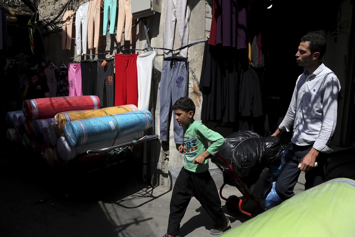 A young worker pulls his hand cart in the main bazaar in Tehran. Depreciation and inflation makes everything more expensive, from fruits and vegetables to tires and oil all the way to the big-ticket items, like mobile phones. (AP Photo/Ebrahim Noroozi)