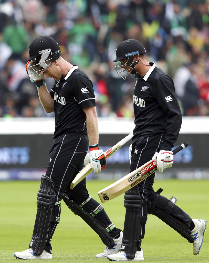 New Zealand's batsman James Neesham, left, with teammate Mitchell Santner leave the crease at the end of their innings during the Cricket World Cup match between New Zealand and Pakistan at the Edgbaston Stadium in Birmingham, England, Wednesday, June 26, 2019. (AP Photo/Rui Vieira)