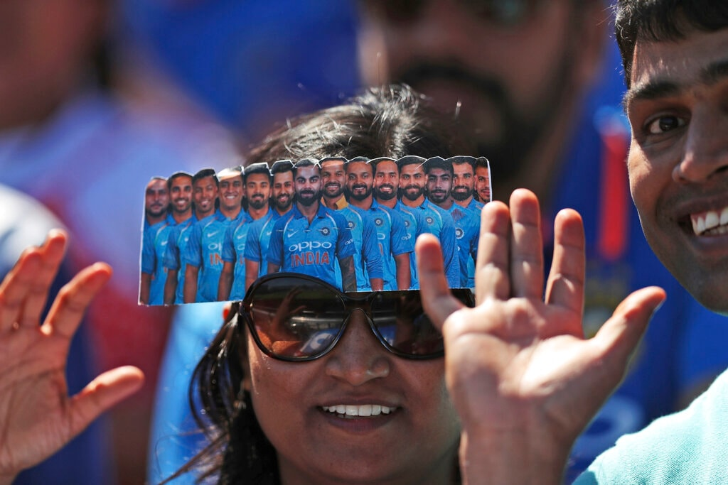A cricket fan has a cutout of the Indian cricket players resting on her forehead during the Cricket World Cup match between India and West Indies at Old Trafford in Manchester, England, Thursday, June 27, 2019. (AP Photo/Jon Super)