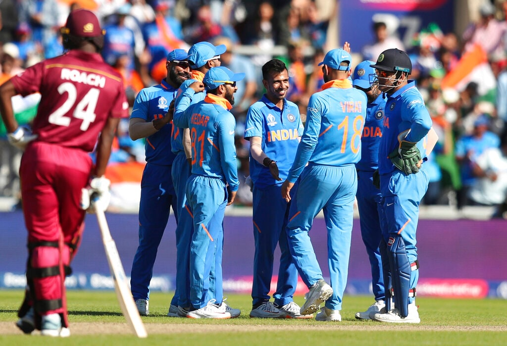 Teammates congratulate India's Yuzvendra Chahal, center, for dismissing West Indies' Sheldon Cottrell the Cricket World Cup match between India and West Indies at Old Trafford in Manchester, England, Thursday, June 27, 2019. (AP Photo/Jon Super)