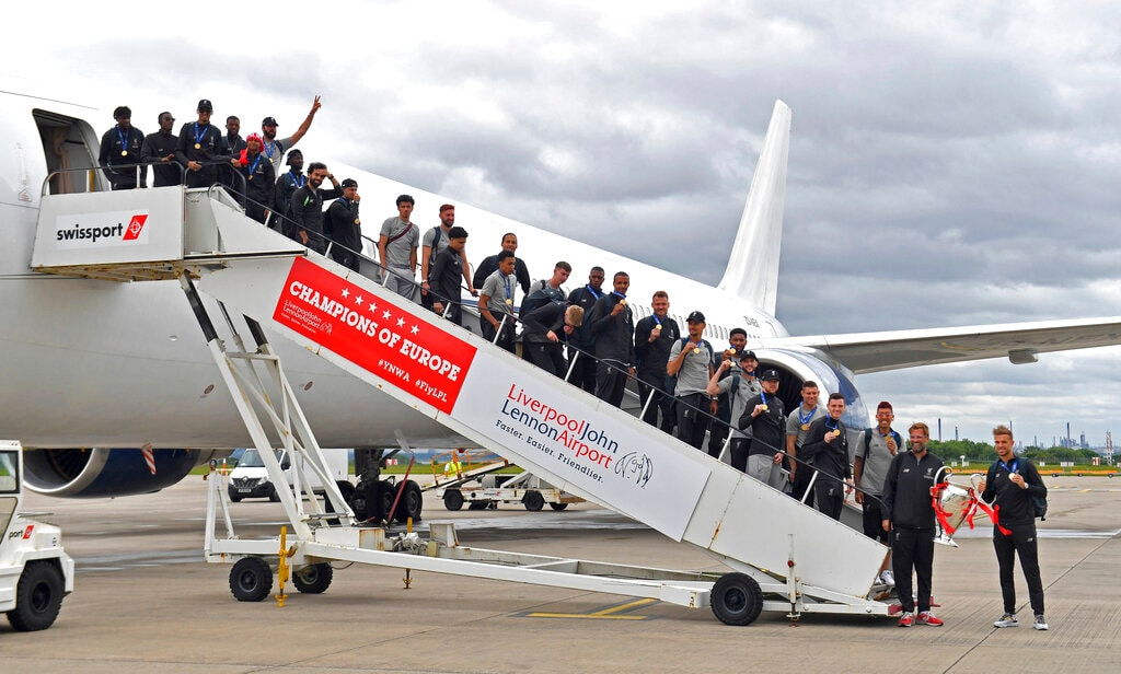 Liverpool pose for a photo with team manager Jurgen Klopp, second right, and captain Jordan Henderson holding the Champions League trophy, as they arrive back to John Lennon Airport in Liverpool, on Sunday. (Dave Howarth/PA via AP)