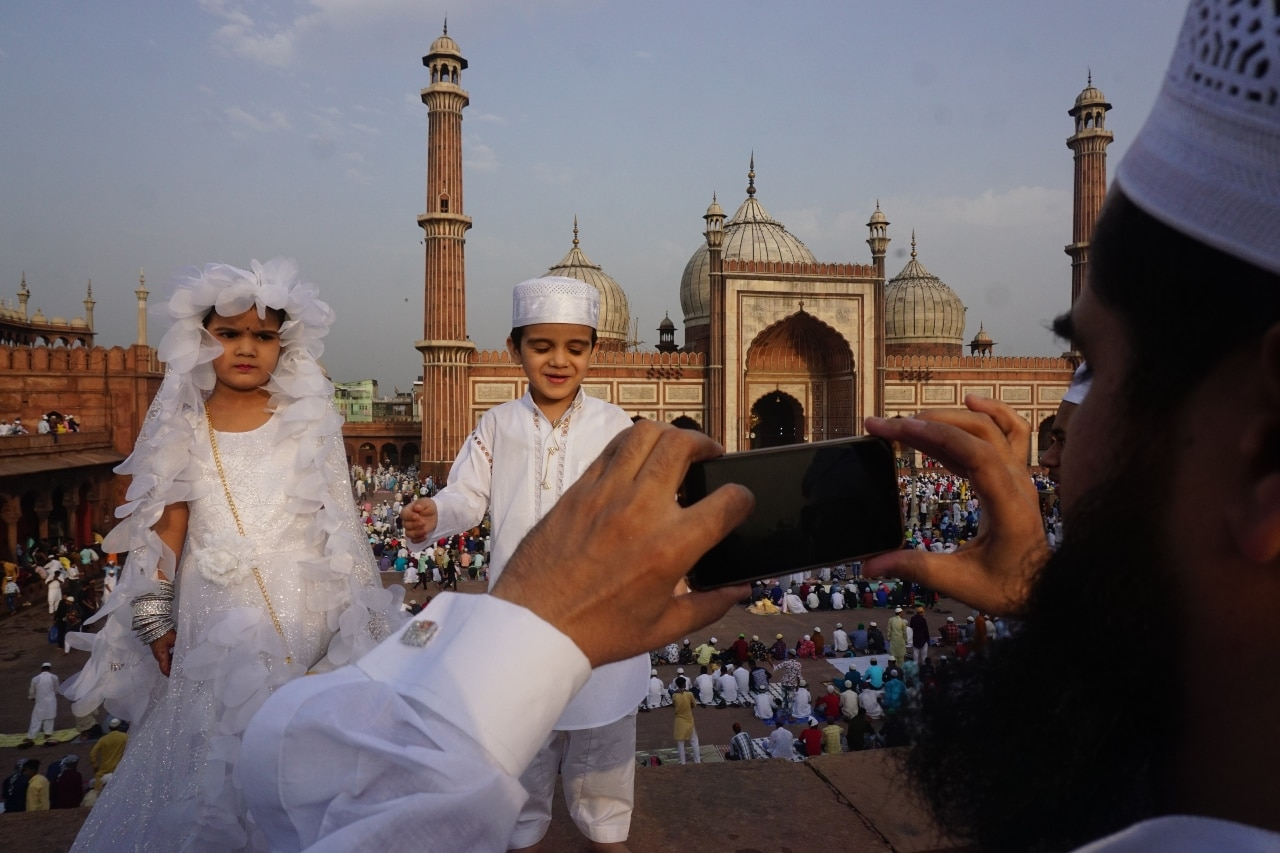 A parent taking pictures of his kids at the Jama Masjid.