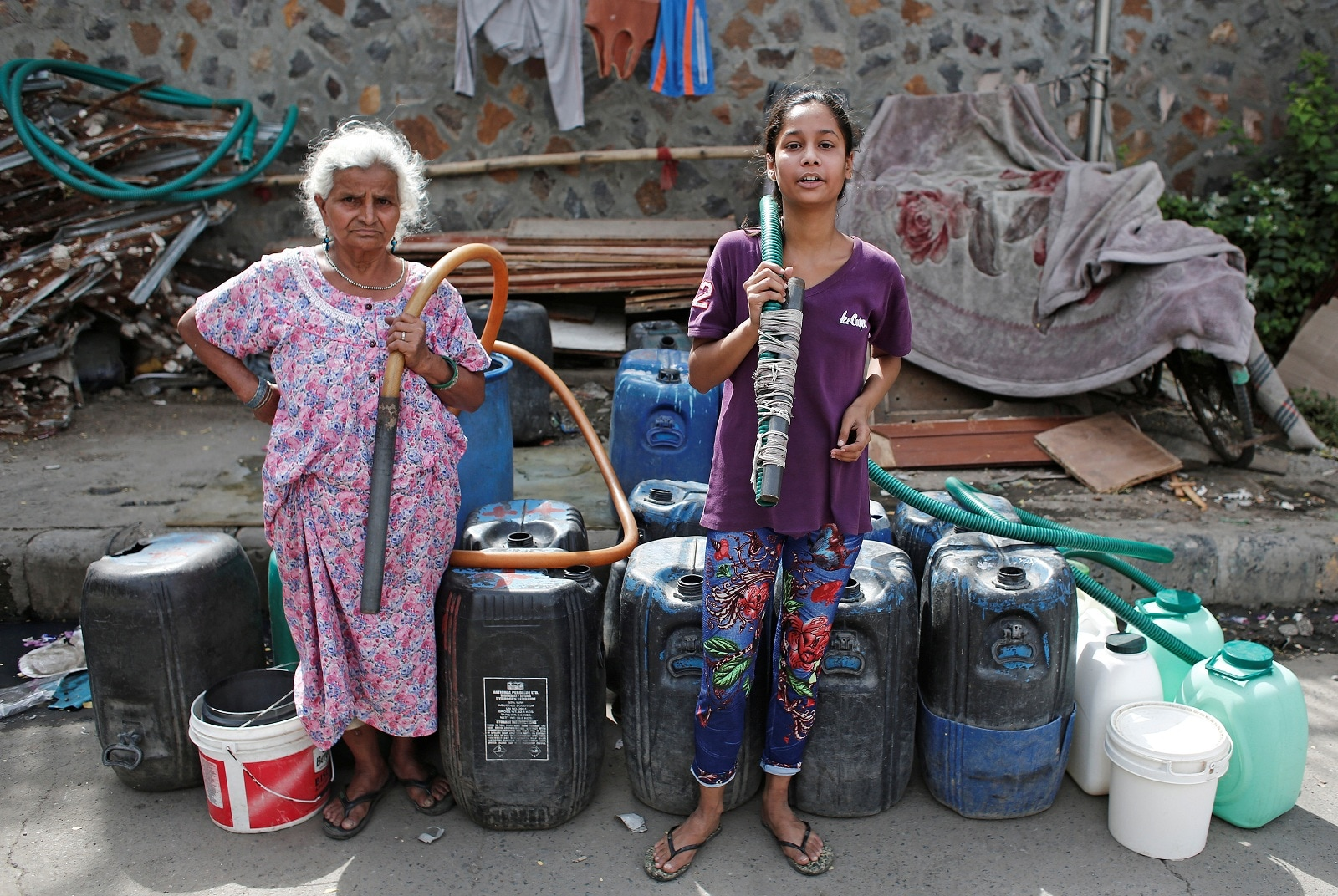 Residents holds pipes as they wait for a municipal water tanker in New Delhi, June 28, 2019. REUTERS/Adnan Abidi/Files