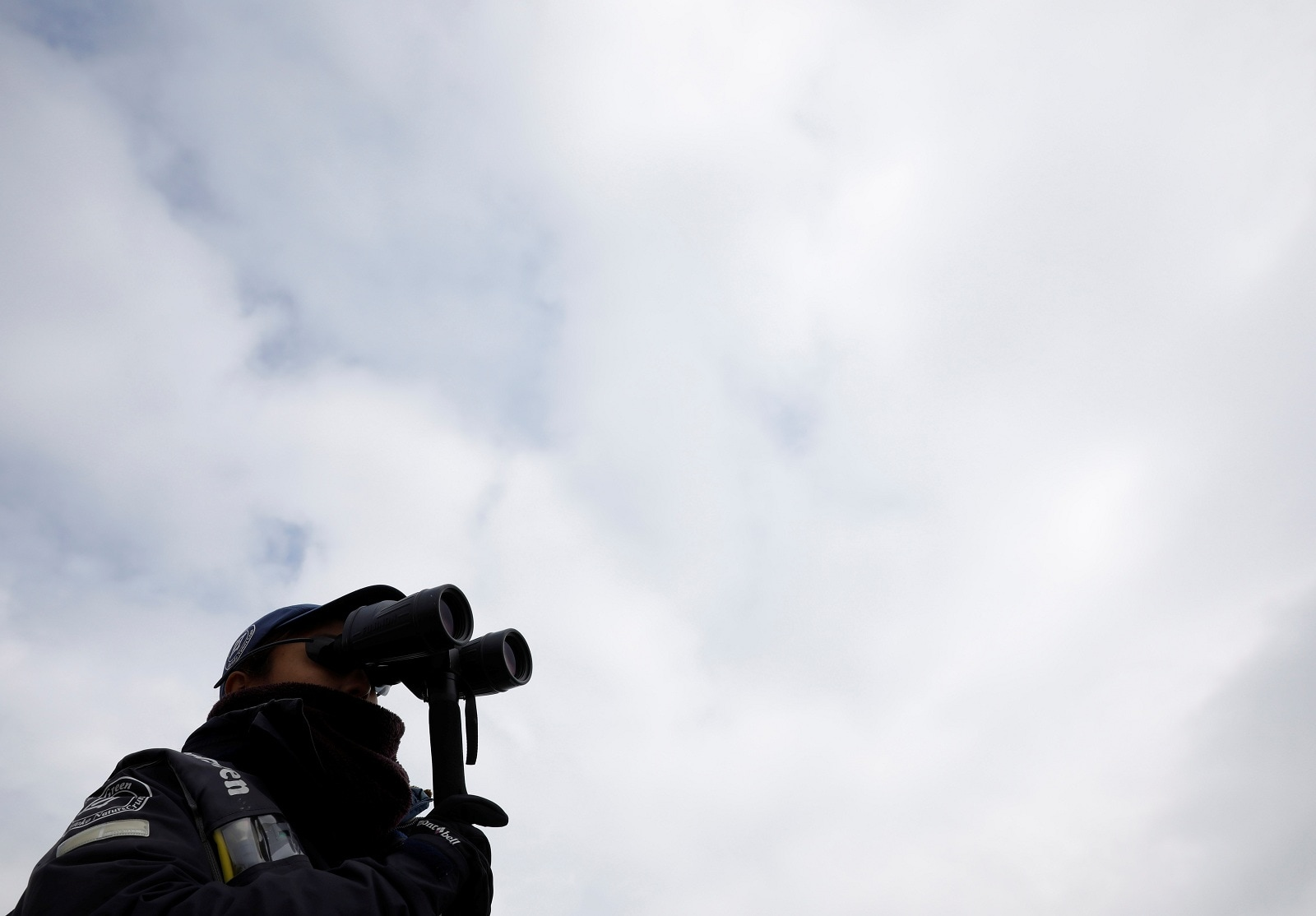 A staff on a whale watching tour boat looks for whales with binoculars in the sea near Rausu, Hokkaido, Japan, July 1, 2019. REUTERS/Kim Kyung-Hoon