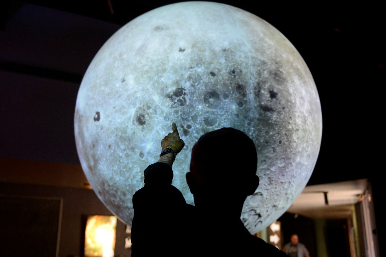 Jack Burns points out locations on a lunar globe at the Fiske Planetarium in Boulder, Colorado, US, June 24, 2019. REUTERS/Michael Ciaglo