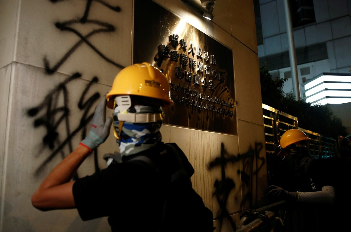 Protesters spray wall of Chinese Liaison Office after a march to call for democratic reforms, in Hong Kong. Black-clad activists, many wearing masks, defied police orders and marched beyond the official end-point of a rally that took place earlier in the day to make their way toward Beijing's Liaison Office, close to the heart of the financial centre.  REUTERS/Edgar Su