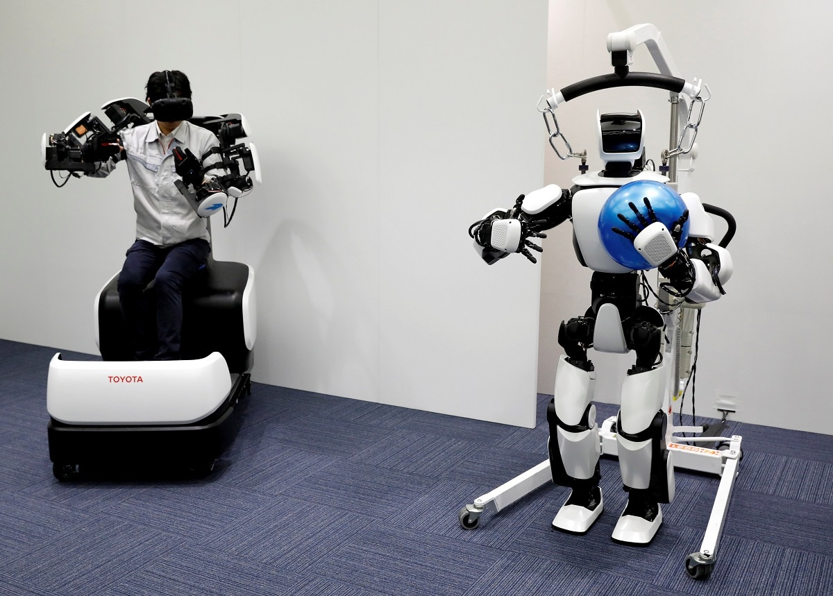 An employee of Toyota Motor Corp. demonstrates a T-HR3 humanoid robot which will be used to support the Tokyo 2020 Olympic and Paralympic Games. REUTERS/Issei Kato