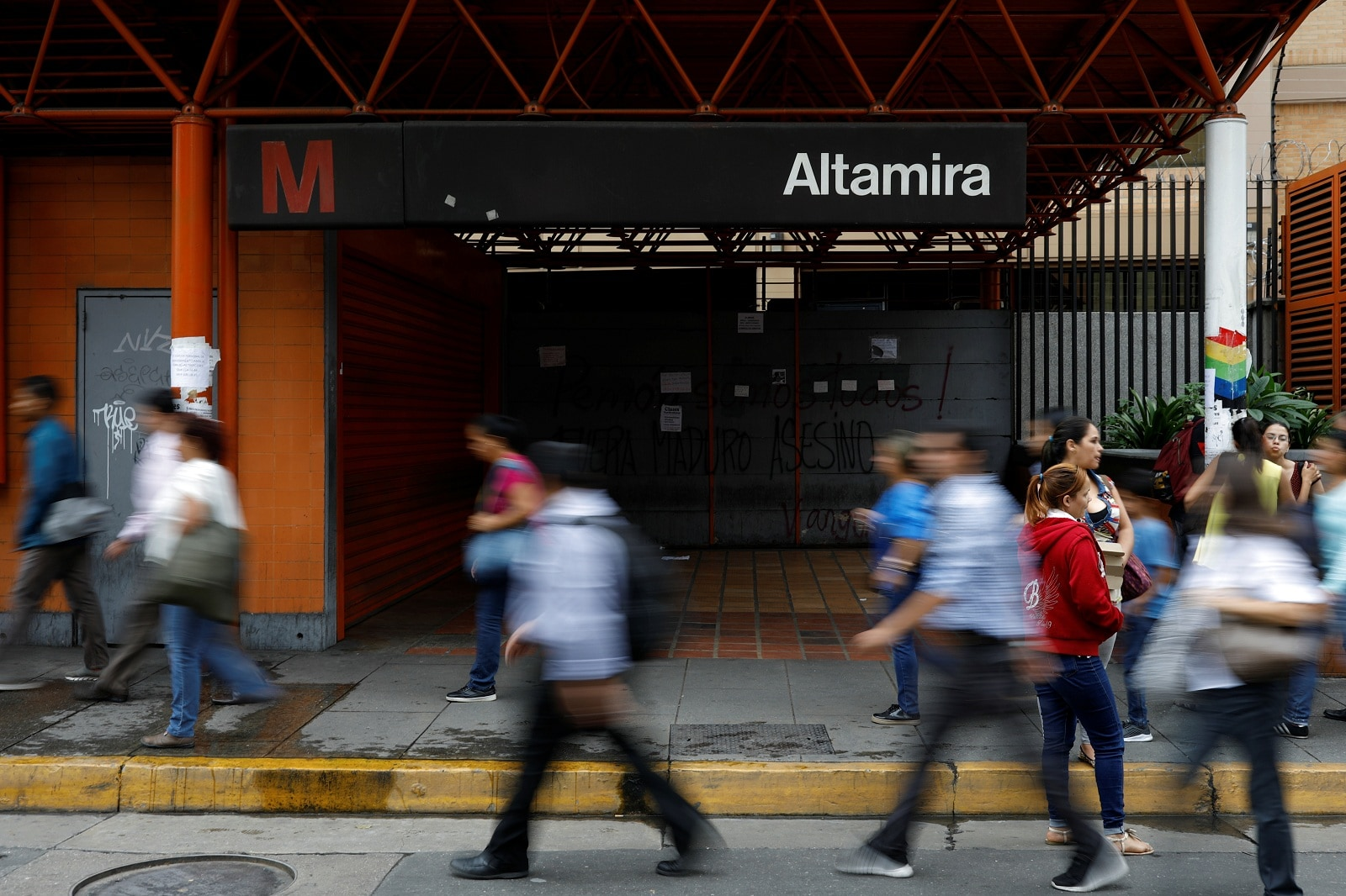 People walk past a closed metro station during a blackout in Caracas, Venezuela July 22, 2019. REUTERS/Carlos Garcia Rawlins