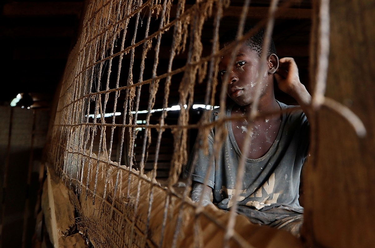 A young informal gold miner glances out from inside a makeshift gold processing room at the site of Nsuaem-Top, Ghana. REUTERS/Zohra Bensemra