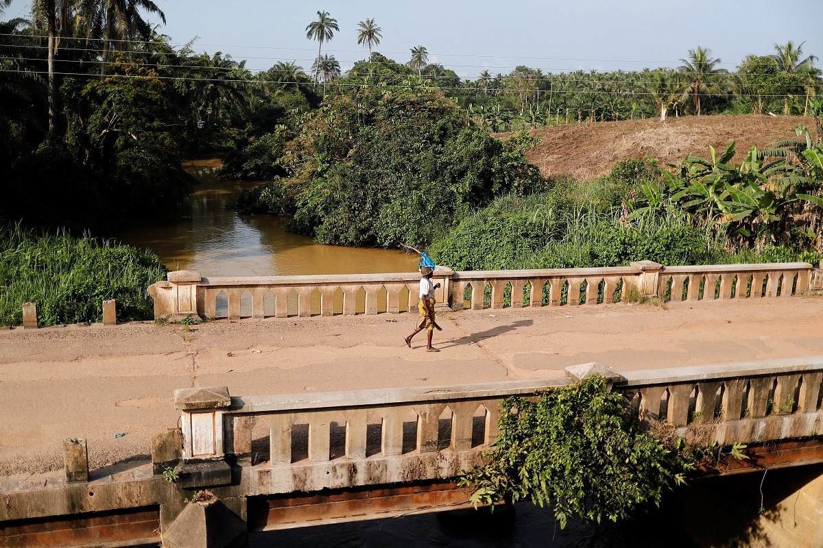 A woman crosses a bridge over a river polluted by gold mining waste. REUTERS/Zohra Bensemra