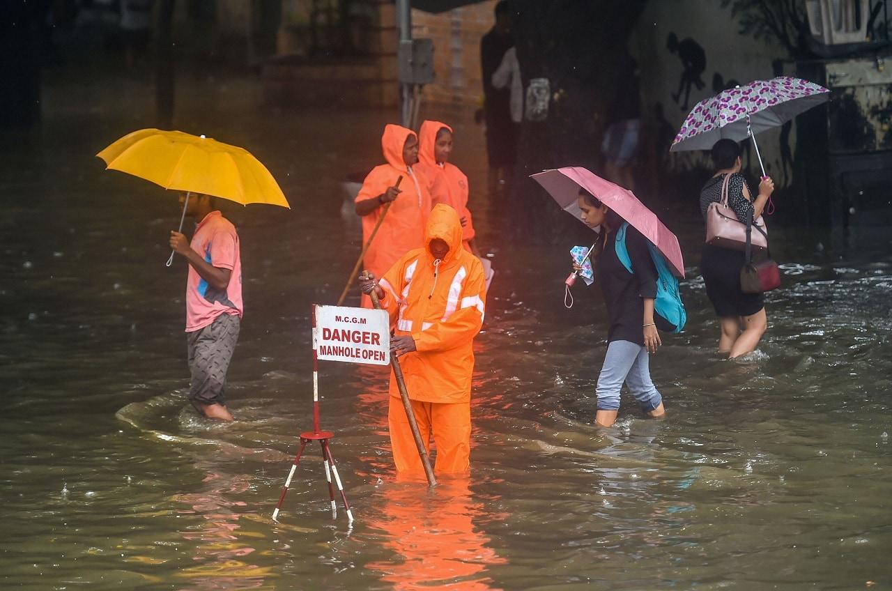 Mumbai: A Municipal worker stands guard to warn pedestrians of an open manhole on a waterlogged street following heavy monsoon rains, in Mumbai, Monday, July 01, 2019. (PTI Photo/Mitesh Bhuvad)