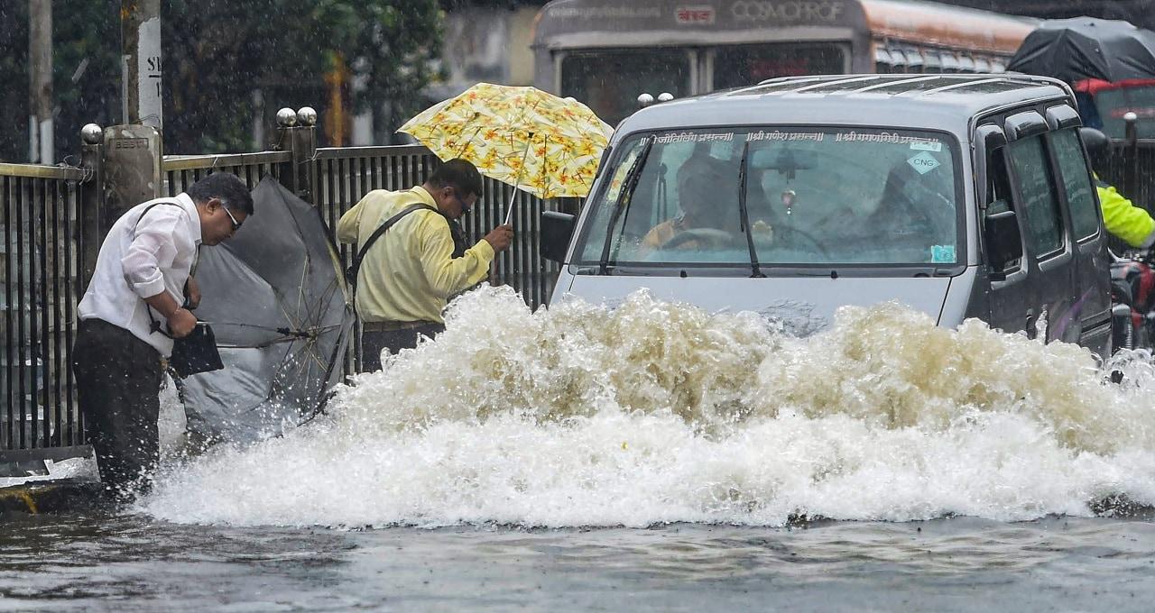 Mumbai: Vehicles move slowly as pedestrians walk through a waterlogged street after heavy monsoon rain, in Mumbai, Monday, July 01, 2019. (PTI Photo/Shashank Parade)