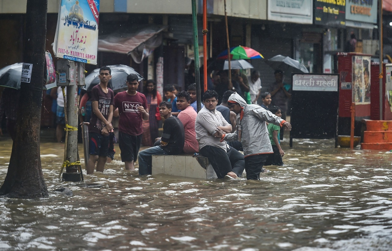 Mumbai: Pedestrians wait on a waterlogged street during heavy monsoon rain, in Mumbai, Monday, July 01, 2019. (PTI Photo/Mitesh Bhuvad)