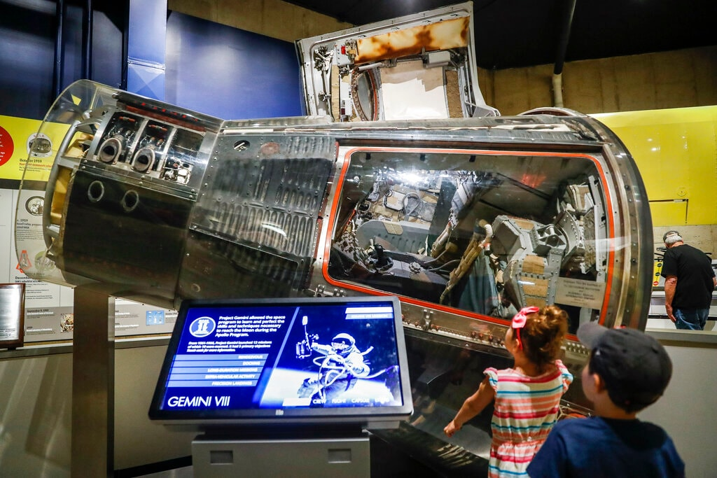 Visitors look on the Gemini VIII spaceship at the Armstrong Air & Space Museum, Wednesday, June 26, 2019, in Wapakoneta, Ohio. Very down to earth about most things, folks in this small western Ohio city are over the moon as they get ready to celebrate the 50th anniversary of the day they watched their hometown hero along with the world set foot on the moon. (AP Photo/John Minchillo)