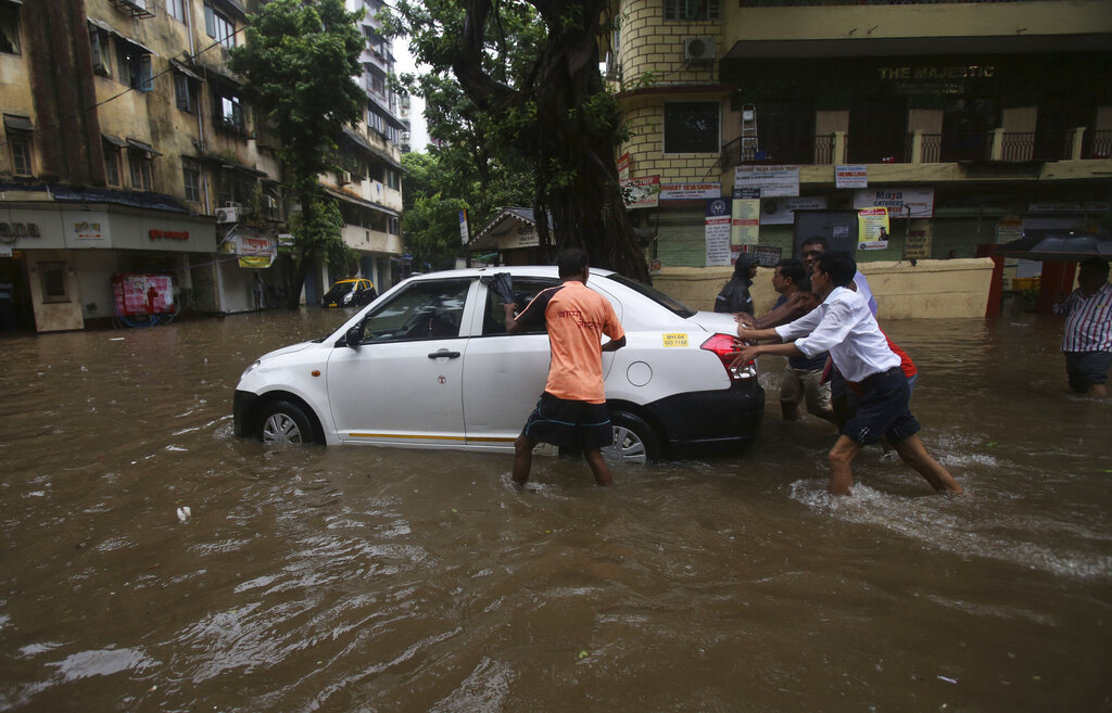 People push a car to a safer place from a waterlogged street during monsoon rains in Mumbai, India, Monday, July 1, 2019. India's monsoon season runs from June to September. (AP Photo/Rafiq Maqbool)