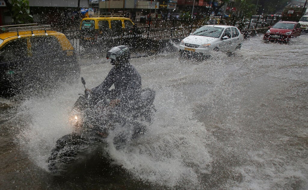 Indians ride through a waterlogged street during monsoon rains in Mumbai, India, Monday, July 1, 2019. India's monsoon season runs from June to September. (AP Photo/Rafiq Maqbool)