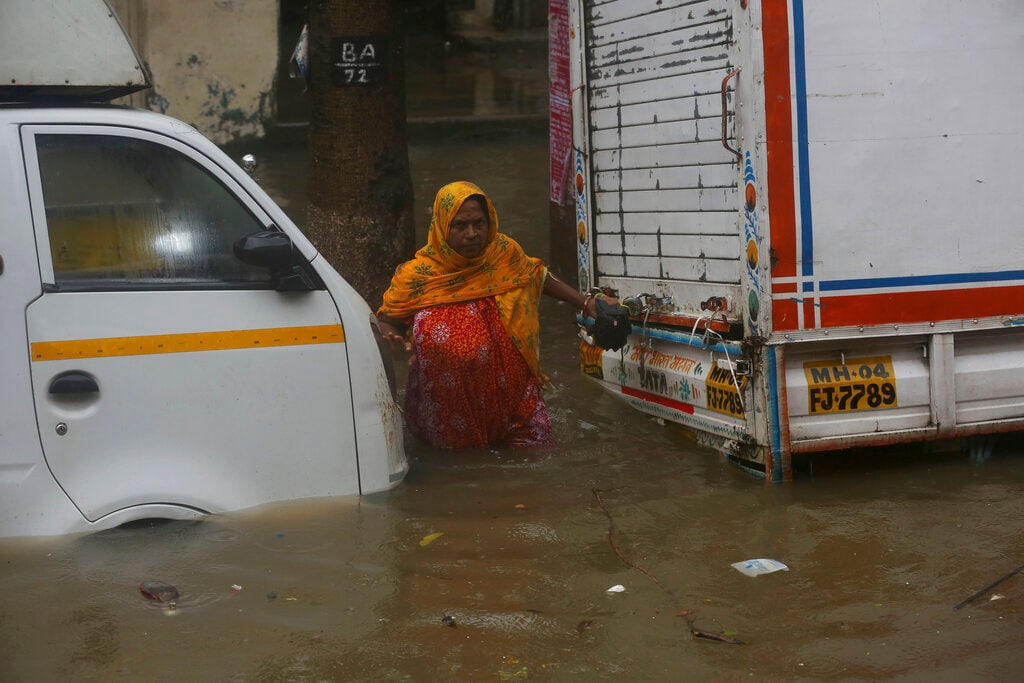 A woman tries to cross through a waterlogged street during monsoon rains in Mumbai, India, Monday, July 1, 2019. India's monsoon season runs from June to September. (AP Photo/Rafiq Maqbool)