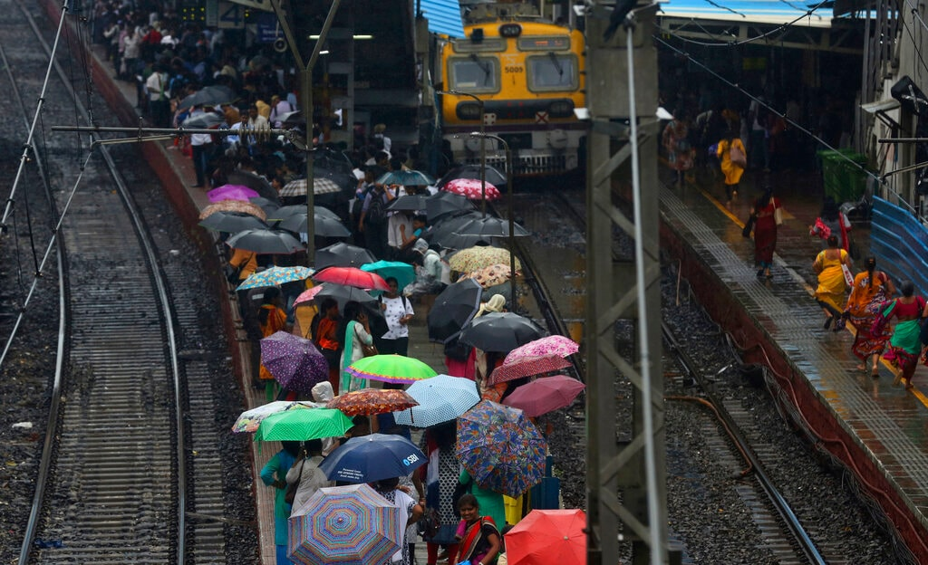 People hold umbrellas as they wait at a station during monsoon rains in Mumbai, India, Monday, July 1, 2019. India's monsoon season runs from June to September. (AP Photo/Rafiq Maqbool)