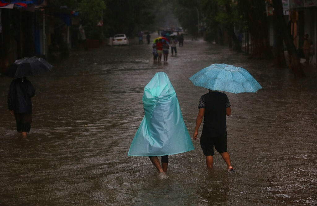 People walk through a waterlogged street during monsoon rains in Mumbai, India, Monday, July 1, 2019. India's monsoon season runs from June to September. (AP Photo/Rafiq Maqbool)