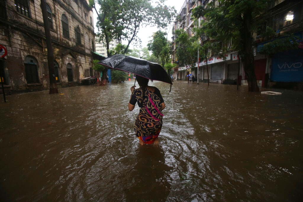 A woman walks through a waterlogged street during monsoon rains in Mumbai, India, Monday, July 1, 2019. India's monsoon season runs from June to September. (AP Photo/Rafiq Maqbool)