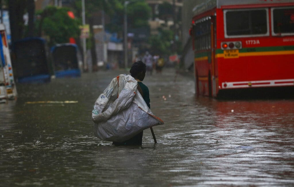 A ragpicker walks looking for recyclable material through a waterlogged street during monsoon rains in Mumbai, India, Monday, July 1, 2019. India's monsoon season runs from June to September. (AP Photo/Rafiq Maqbool)