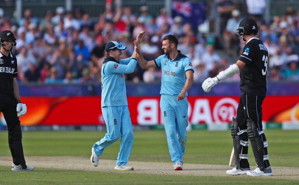 England's Mark Wood, center right, celebrates with captain Eoin Morgan the dismissal of New Zealand's Mitchell Santner during the Cricket World Cup match between New Zealand and England in Chester-le-Street, England, Wednesday, July 3, 2019. (AP Photo/Scott Heppell)