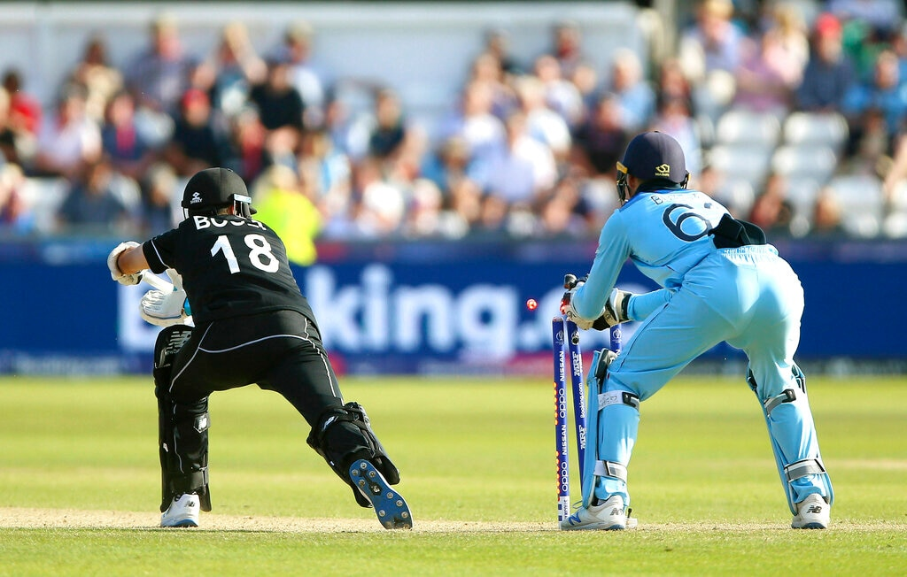 England's Jos Buttler, right, takes the wicket of New Zealand's Trent Boult during the Cricket World Cup match between New Zealand and England in Chester-le-Street, England, Wednesday, July 3, 2019. (Nigel French/PA via AP)