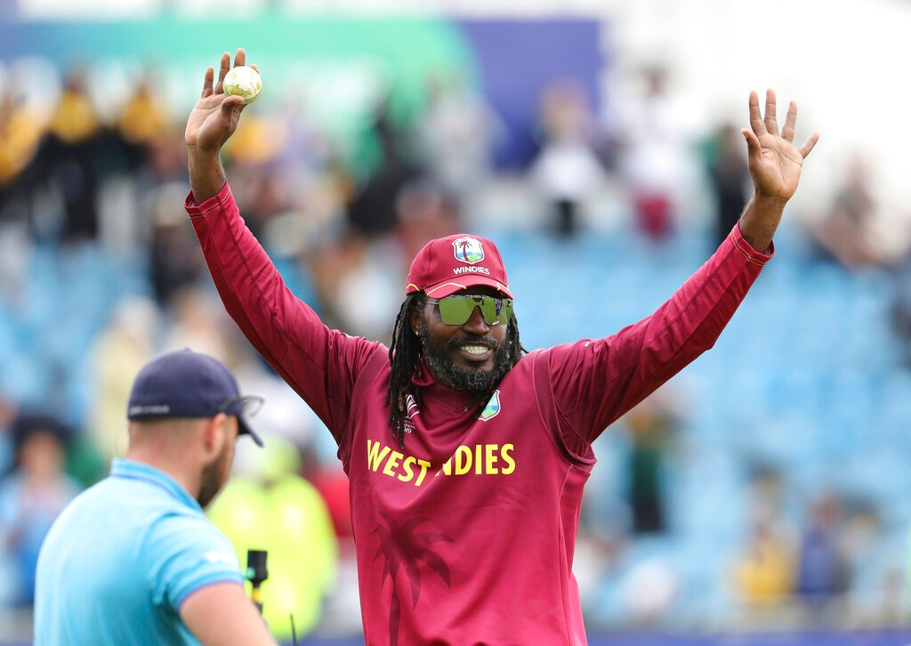 West Indies' Chris Gayle holds the ball as he leaves the ground after their win over Afghanistan in the Cricket World Cup match at Headingley in Leeds, England, Thursday, July 4, 2019. (AP Photo/Rui Vieira)