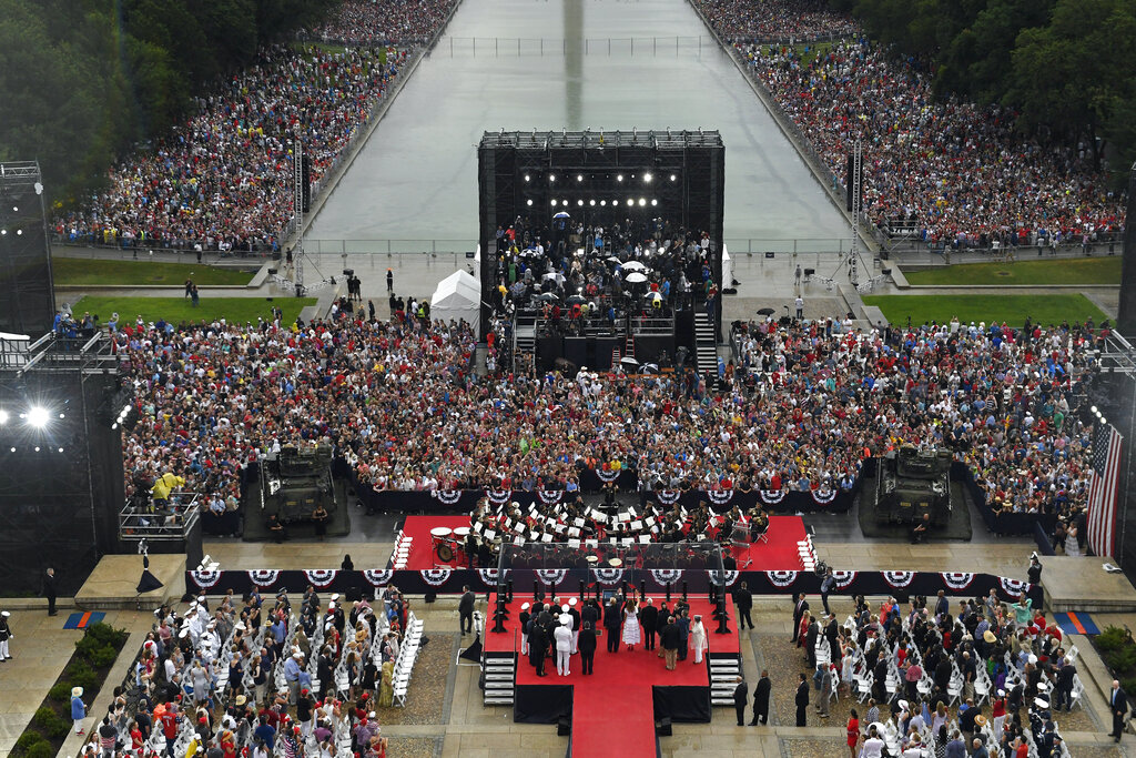 President Donald Trump, standing with first lady Melania Trump and others, waves to the crowd following his speech at an Independence Day celebration in front of the Lincoln Memorial in Washington, Thursday, July 4, 2019. (AP Photo/Susan Walsh, Pool)