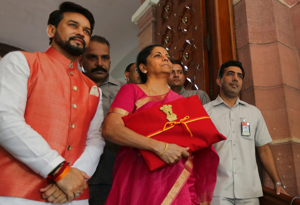 Finance Minister Nirmala Sitharaman, center, and junior Finance Minister Anurag Thakur, left stands for the media at the parliament house before presenting the Union budget in New Delhi, Friday, July 5, 2019. The government said that it will raise part of its gross borrowing in external markets in foreign currencies. (AP Photo/Manish Swarup)