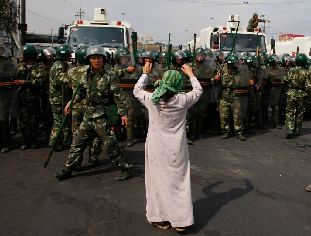 A Uighur woman protests before a group of paramilitary police when journalists visited the area in the aftermath of riots in Urumqi in western China's Xinjiang region. Tuesday, July 7, 2009. (AP Photo/Ng Han Guan)