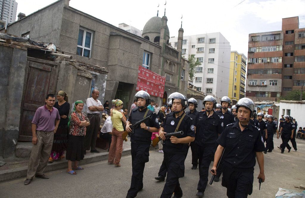 Heavily armed Chinese police officers patrol near a mosque in a Uighur neighborhood in the aftermath of riots in Urumqi in western China's Xinjiang region. July 8, 2009. (AP Photo/Ng Han Guan, File)
